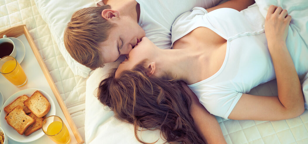 Man and Woman on Bed Kissing with Breakfast